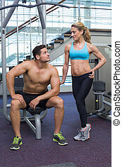 Bodybuilding man and woman smiling at each other