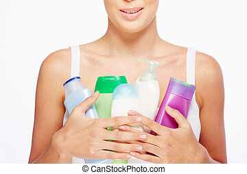 Close-up of young woman holding containers with bodycare products