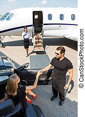 Bodyguard Assisting Elegant Woman Stepping Out Of Car