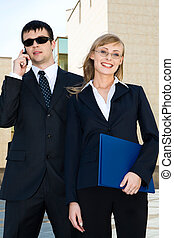 Beautiful smiling blond woman holding document-case in her hands and big man in sunglasses talking by the cell phone behind her