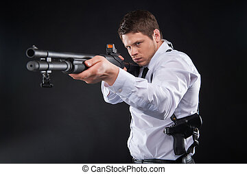 Bodyguard. Serious young man in shirt and tie holding gun ...