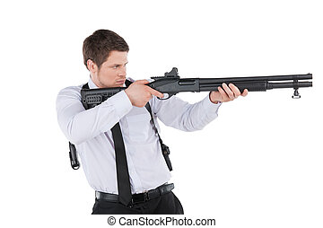 Bodyguard. Side view of confident young man in shirt and tie aiming with the gun and looking at camera while standing isolated on white