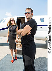 Bodyguard Standing Against Elegant Woman And Private Jet