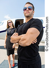 Bodyguard Standing Against Woman And Private Jet - Bodyguard...