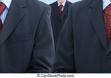 Three male trunks in dark suits with red neckties
