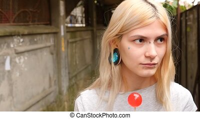 bodymification. a girl with a split tongue licks lollipop....