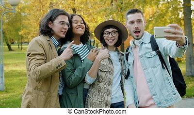 boeiend, vrolijke , toeristen, selfie, het tonen, vrienden, park, duim-omhoog, verticaal