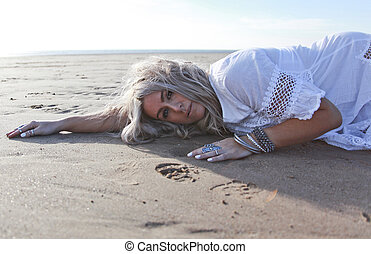 Beautiful blonde haired woman dressed in boho style at the beach