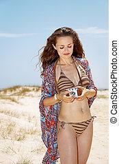 Bohemian young woman on white beach adjusting retro photo camera