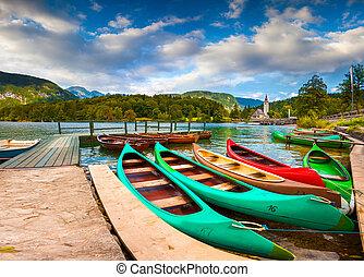 Bohinj Lake with boats and Church of St John the Baptist, Triglav National Park, Julian Alps, Slovenia.