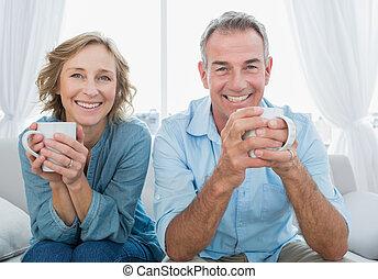 bohnenkaffee, paar, haben, couch, lächeln, mittelalt, sitzen