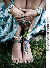 boho fashion details woman hands and bare feet on grass with...