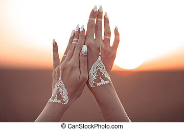 Boho style white hand tattoo. Bohemian woman carefree at the sunset, outddoor photo.