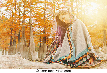 Boho style young woman wearing in poncho resting on tree trunk near the cypresses in autumn on sunny day.