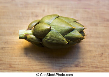 Boiled artichoke isolated on wooden background