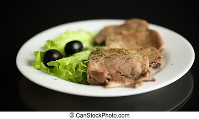 boiled beef tongue sliced in a plate boiled beef tongue sliced in a plate on black background