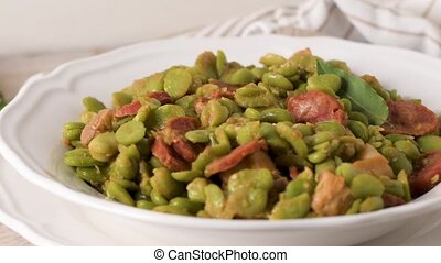 Boiled broad bean with chorizo and laurel leaves on a white...