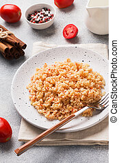 Boiled bulgur with tomatoes in a ceramic plate.