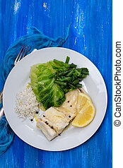 boiled cod fish with rice and vegetables on white plate