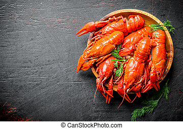 Boiled crayfish on a wooden plate with dill.