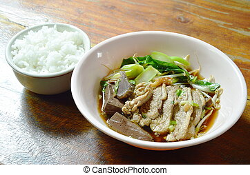 boiled duck meat and blood in brown Chinese herb soup on bowl eat couple with rice