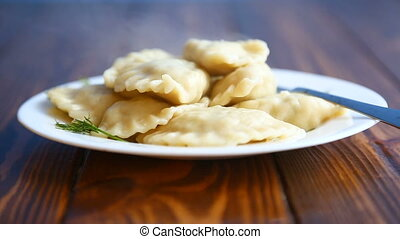 Boiled dumplings stuffed - steamed hot dumplings on a wooden...