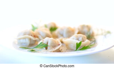 boiled dumplings with meat and spices in a plate on a white...