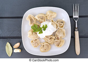 boiled dumplings with sour cream on a plate, top view, fork
