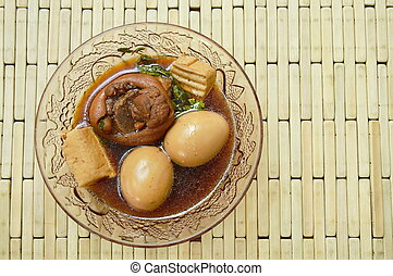 boiled egg with pork leg in herb brown soup on glass bowl