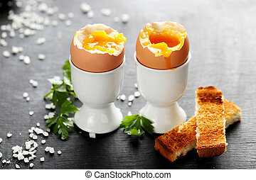 Boiled egg with toasts on a black wooden table