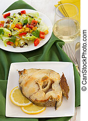 boiled fish with lemon on the white plate