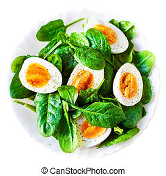 Boiled halved eggs on plate decorated with spinach leaves...