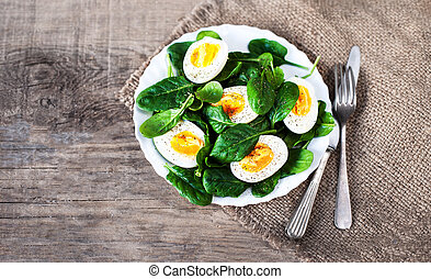 Boiled halved eggs on plate decorated with spinach leaves ...