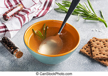 Boiled meat broth in a plate with spices garlic and rosemary.