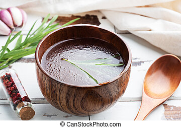 Boiled meat broth in a wooden plate with spices garlic and rosemary.