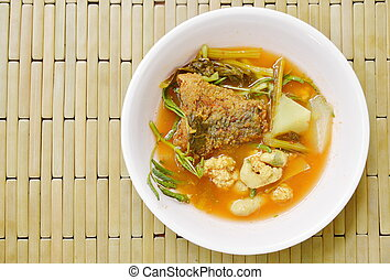 boiled mixed vegetable topping fried fish and egg in Thai spicy soup on bowl