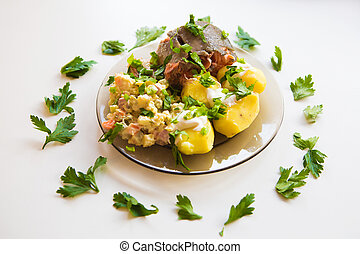 Boiled potatoes under sour cream, red fish, salad sprinkled with parsley on a plate of dark glass