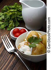 Boiled potatoes with cherry tomatoes, parsley and sour cream on wooden table