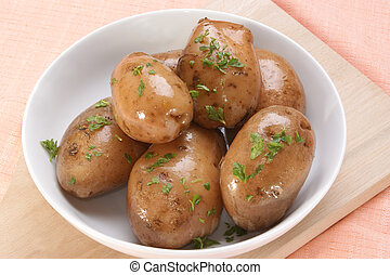 Boiled potatoes with chopped parsley in a bowl