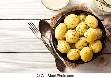 Boiled potatoes with dill in bowl on white wooden background.