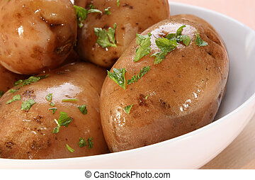 boiled potatoes with parsley in a white bowl