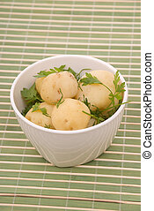 Boiled potatoes with parsley on a bamboo