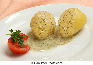 boiled potatoes with parsley sauce on a plate