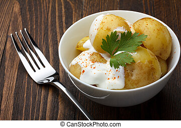 Boiled potatoes with sour cream on wooden table still life
