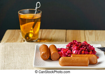 Boiled Sausages with salad on a plate a glass of tea austere breakfast.