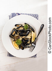 boiled scottish mussels in a deep dish with parsley and lemon