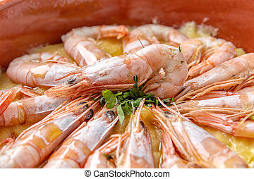 Boiled shrimp symmetrically laid in a plate. With green parsley.