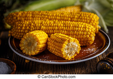Boiled sweet corn on brown plate, close up