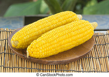 Boiled sweet corn on the wooden plate