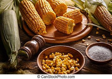 Boiled sweet corn on wooden board